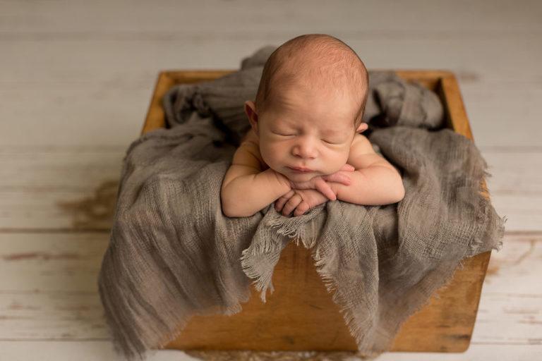Baby in Holzkiste beim Newborn Shooting in Esslingen