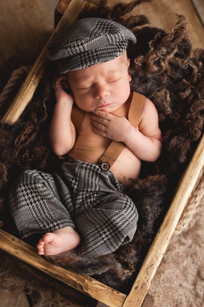 Neugeborenenfotografie mit Latzhose und Schiebermützchen